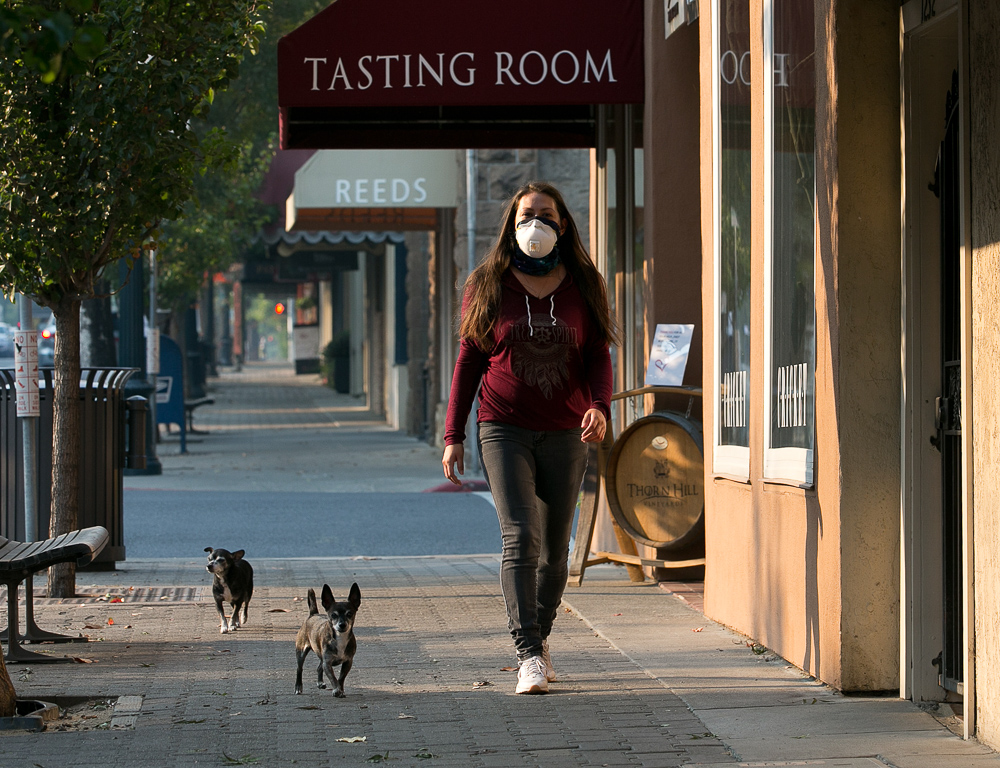 <div class='meta'><div class='origin-logo' data-origin='none'></div><span class='caption-text' data-credit='Rich Pedroncelli/AP Photo'>Vianey Zaldiver wears a mask due to the smoke in the area as she and her dogs walk the deserted sidewalk of downtown St Helena, Calif. Friday, Oct. 13, 2017.</span></div>