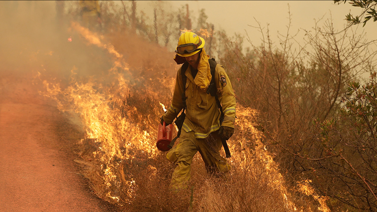 A Sonoma City firefighter walks in front of flames during a backburn operation Friday, Oct. 13, 2017, in Glen Ellen, Calif.