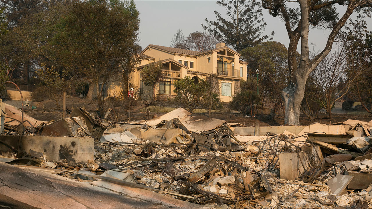 A large home that survived last week's wildfire sits by the burned ruins of a nearby home, Monday, Oct. 16, 2017, in Santa Rosa, Calif.
