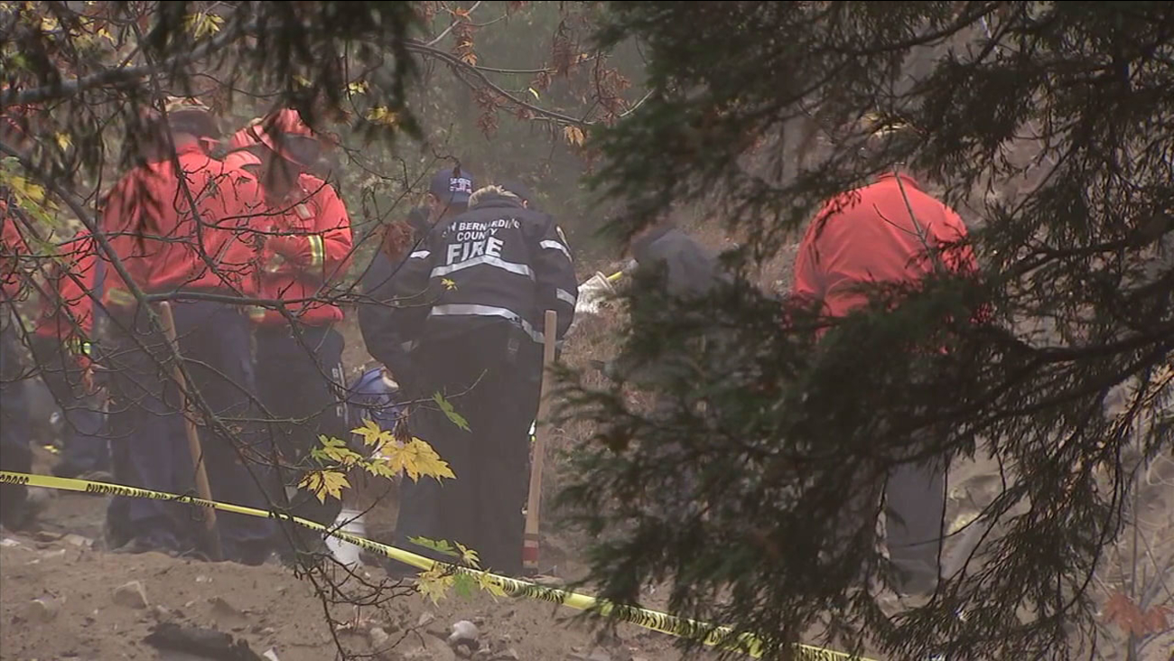Authorities examine the scene in Crestline where the discovery of a human hand sticking up from the ground led to the body of a woman who died in a cave collapse.