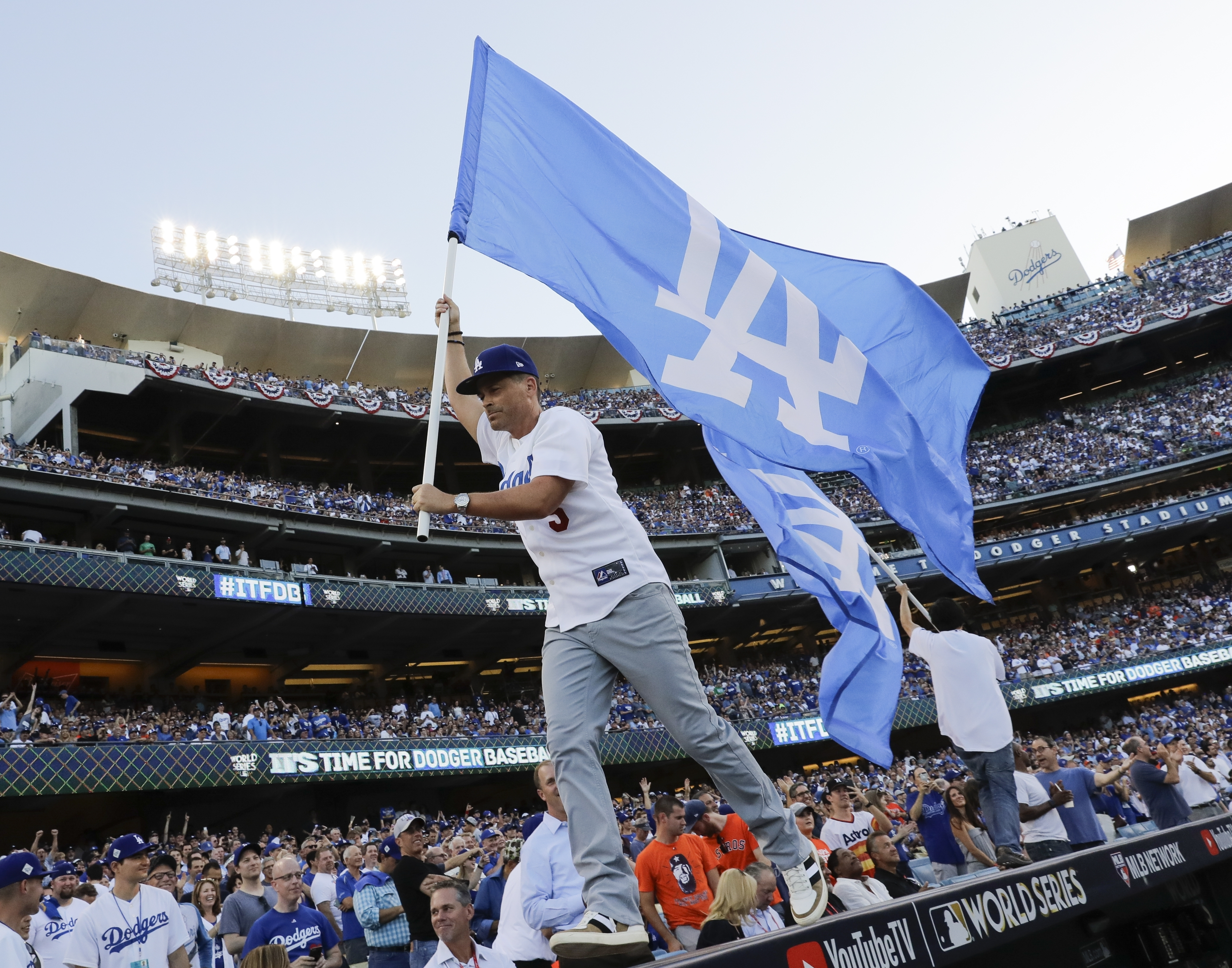 <div class='meta'><div class='origin-logo' data-origin='AP'></div><span class='caption-text' data-credit='(AP Photo/David J. Phillip)'>Actor Rob Lowe runs with a flag before Game 1 of baseball's World Series between the Houston Astros and the Los Angeles Dodgers Tuesday, Oct. 24, 2017, in Los Angeles.</span></div>