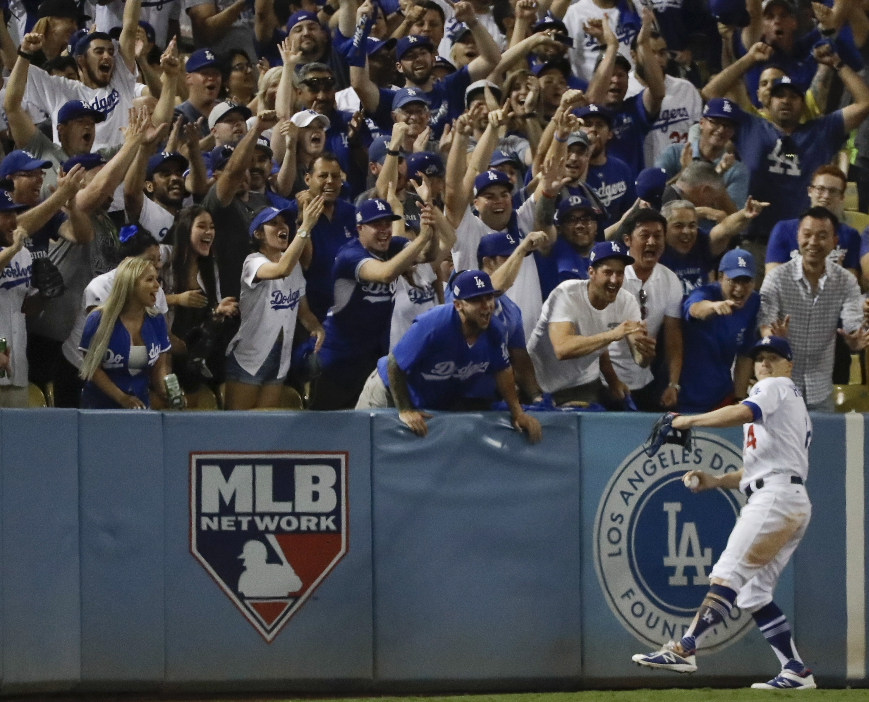 <div class='meta'><div class='origin-logo' data-origin='AP'></div><span class='caption-text' data-credit='(AP Photo/David J. Phillip)'>Fans cheer as Los Angeles Dodgers' Enrique Hernandez catches a long fly ball hit by Houston Astros' Josh Reddick during the eighth inning of Game 1 of baseball's World Series.</span></div>