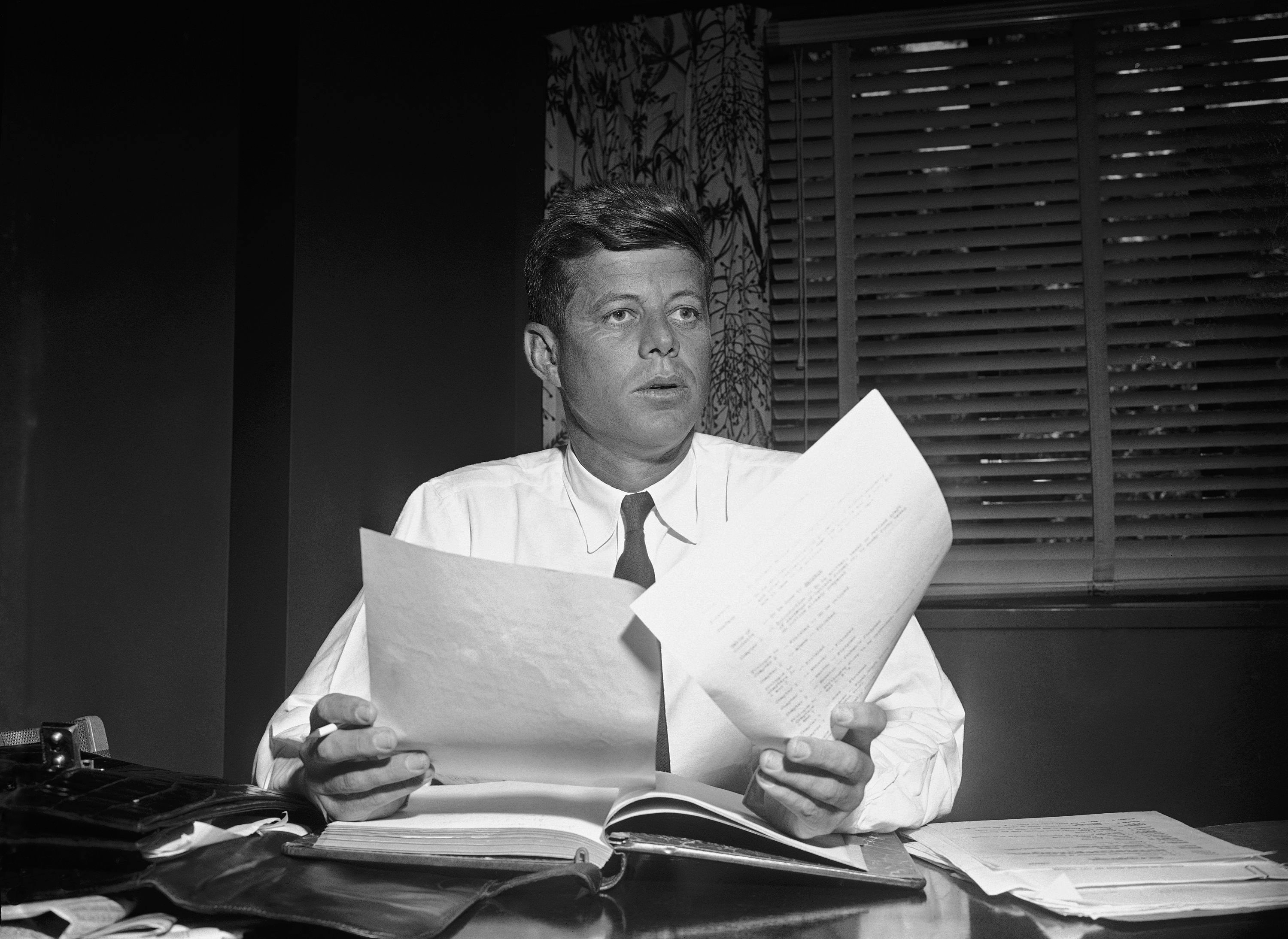 <div class='meta'><div class='origin-logo' data-origin='none'></div><span class='caption-text' data-credit='AP Photo/Bill Allen'>Sen. John Kennedy (D-Mass) as he catches up on his work in his hotel suite, May 24, 1955 after returning to the capital after an eight-month absence, following an operation.</span></div>