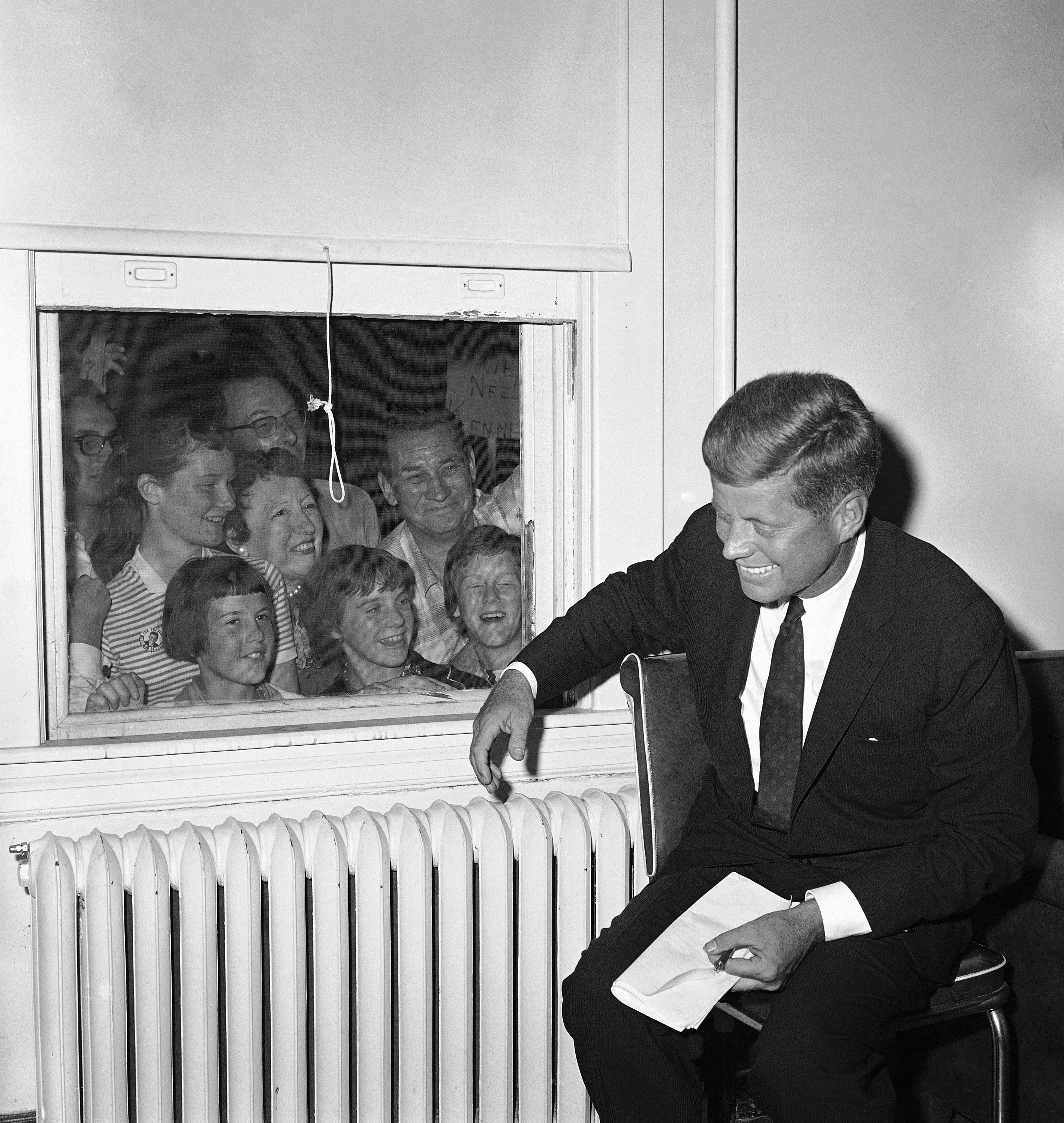 <div class='meta'><div class='origin-logo' data-origin='none'></div><span class='caption-text' data-credit='ASSOCIATED PRESS'>Seeking a look at a presidential possibility, people jam the window behind Sen. Jack F. Kennedy, the Democratic nominee in Baltimore, Maryland, Sept. 16, 1960.</span></div>
