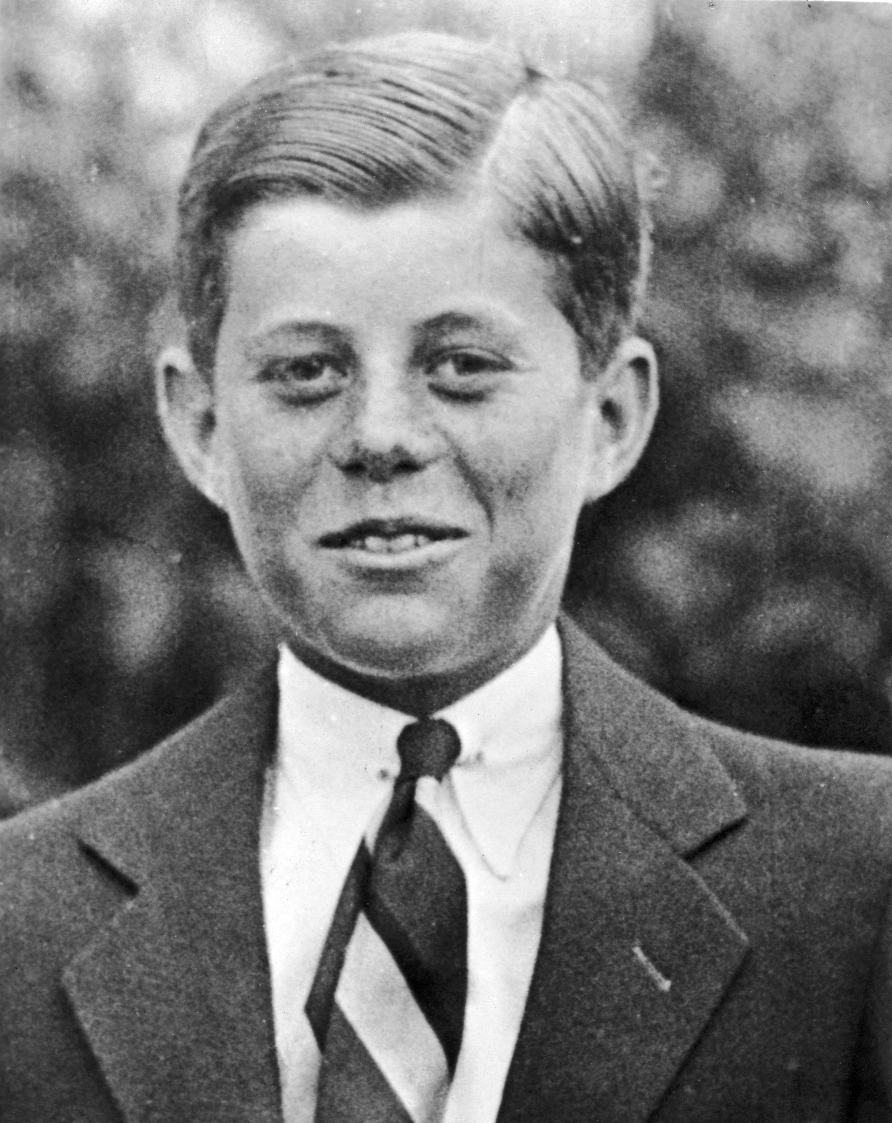 <div class='meta'><div class='origin-logo' data-origin='none'></div><span class='caption-text' data-credit='ulton Archive/Getty Images'>1927:  Headshot portrait of John F Kennedy (1917-1963) at age ten, standing outdoors and wearing a suit with his hair slicked back.</span></div>