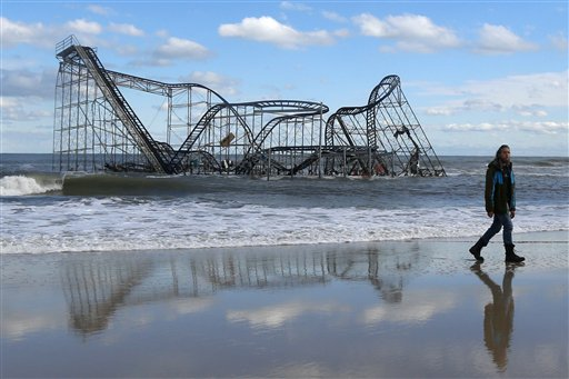 <div class='meta'><div class='origin-logo' data-origin='none'></div><span class='caption-text' data-credit='AP'>John Okeefe walks on the beach as a rollercoaster that once sat on the Funtown Pier in Seaside Heights, N.J., rests in the ocean on Wednesday, Oct. 31, 2012</span></div>