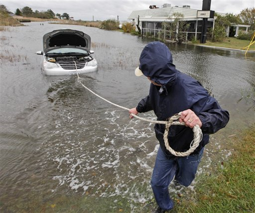 <div class='meta'><div class='origin-logo' data-origin='none'></div><span class='caption-text' data-credit='AP'>Glenn Heartley pulls on a rope attached to his car in preparation for getting it towed from a creek in Chincoteague, Va., Tuesday, Oct. 30, 2012.</span></div>