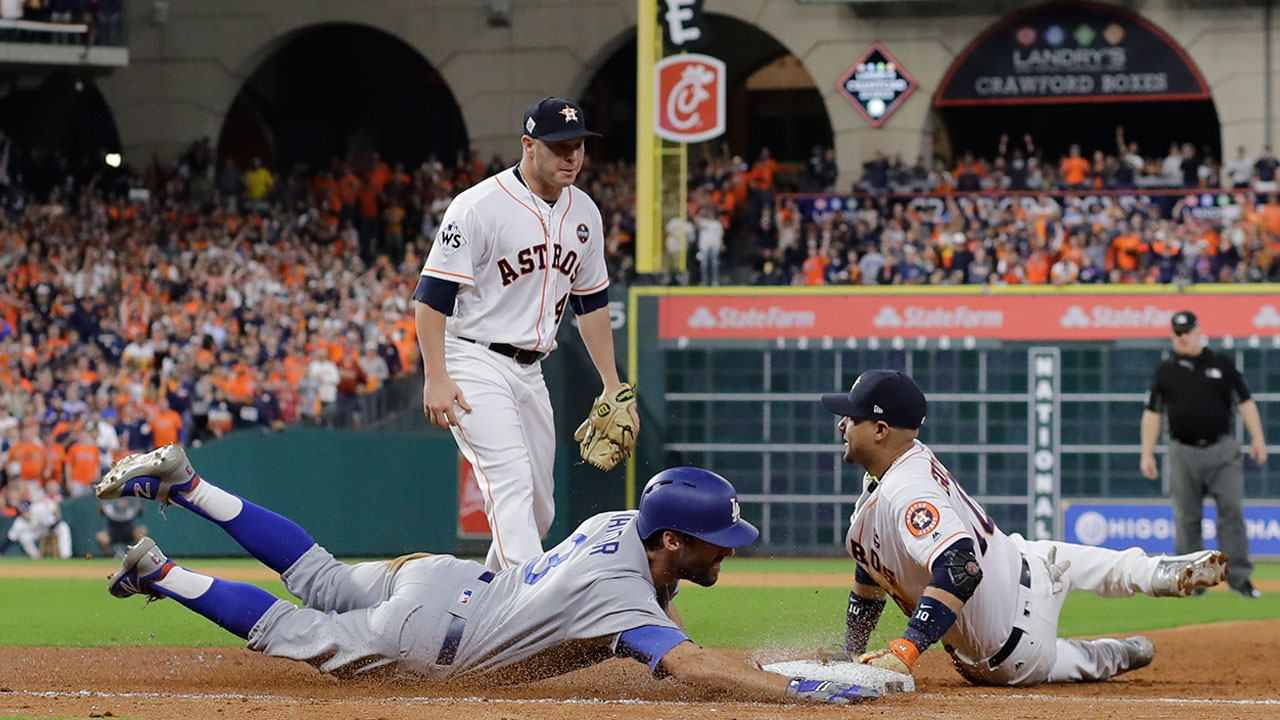 Houston Astros' Yuli Gurriel dives to first to force out Los Angeles Dodgers' Chris Taylor during Game 3 of the World Series Friday, Oct. 27, 2017, in Houston.