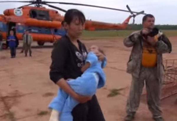 "<div class=""meta image-caption""><div class=""origin-logo origin-image ""><span></span></div><span class=""caption-text"">After losing her shoes and having severely scratched feet, Karina's mother carries her through an airfield before boarding a plane. (Photo/Ministry of Emergency Situations in Republic Sakha)</span></div>"