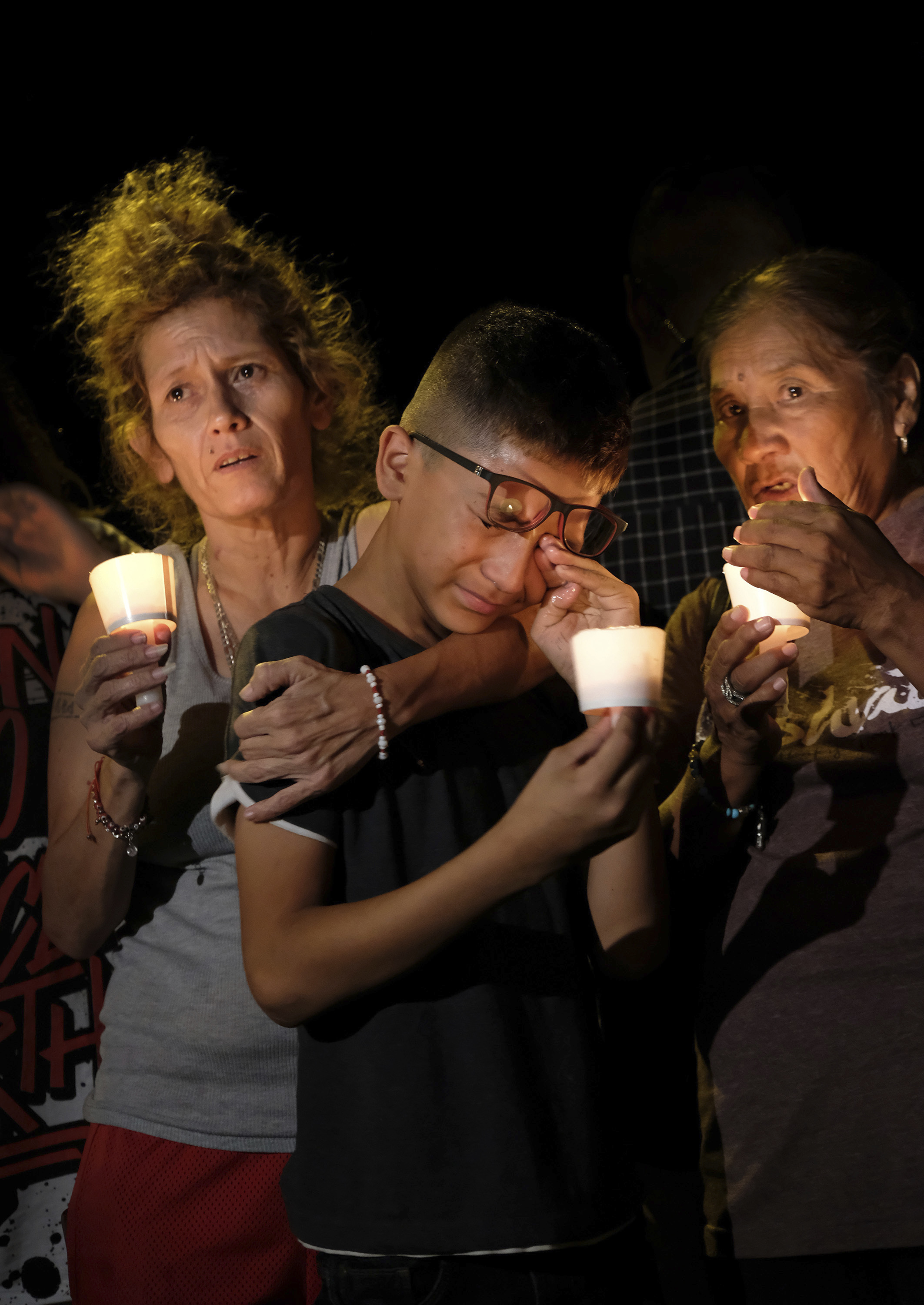 <div class='meta'><div class='origin-logo' data-origin='none'></div><span class='caption-text' data-credit='Laura Skelding/AP'>Mona Rodriguez, Jayanthony Hernandez, 12 and Juanita Rodriguez, from left, participate in a candlelight vigil held for the victims of the shooting.</span></div>