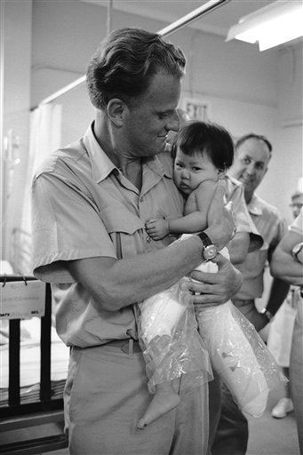 "<div class=""meta image-caption""><div class=""origin-logo origin-image ap""><span>AP</span></div><span class=""caption-text"">Evangelist Billy Graham holds a small Vietnamese Girl, who is having her legs treated, during a visit to the U.S. 3rd field hospital in Saigon Dec. 21, 1966.</span></div>"