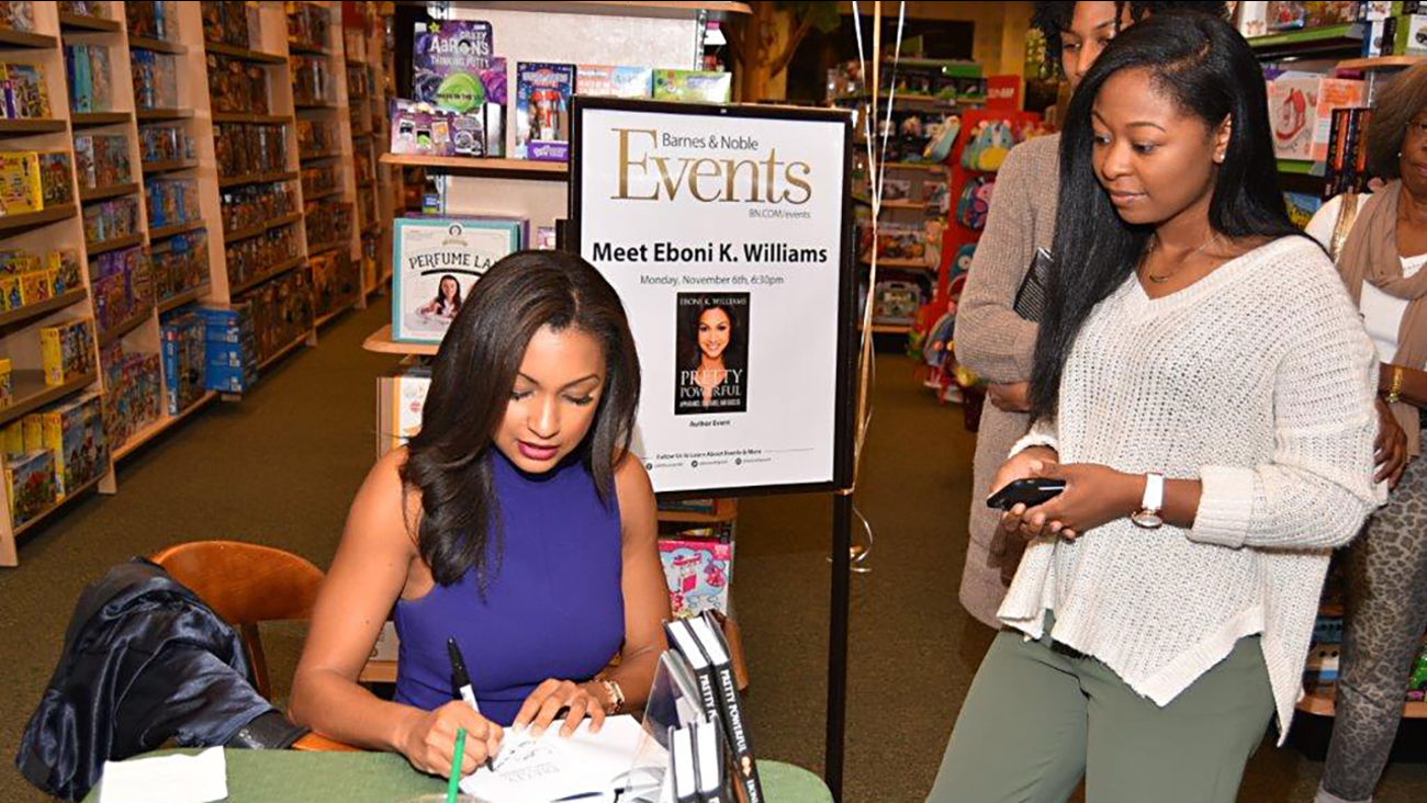 Eboni K. Williams signs a book for recent NCCU Grad Courtney Woods on Monday in Durham.
