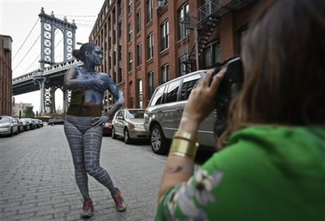 "<div class=""meta image-caption""><div class=""origin-logo origin-image ""><span></span></div><span class=""caption-text"">Merry taking a shot of her model in Dumbo, Brooklyn. (Rachelle Bidner / AP)</span></div>"