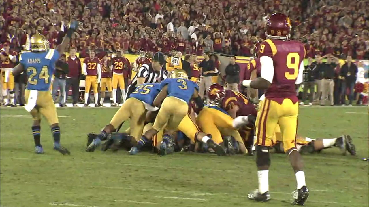 USC and UCLA football players pile up during a football game in this image.
