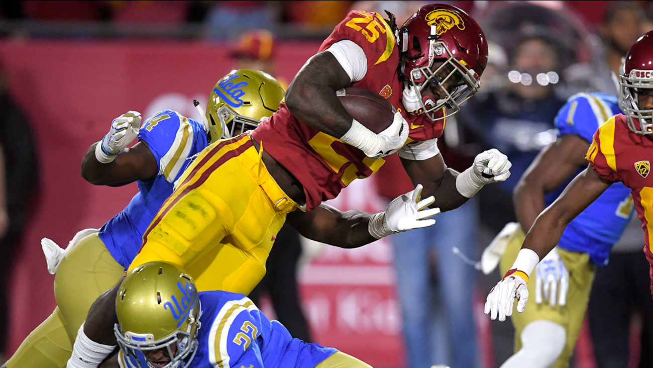 USC running back Ronald Jones II, top, is tackled by UCLA defensive back Nate Meadors during their game, Saturday, Nov. 18, 2017, in Los Angeles.