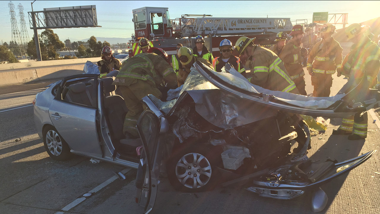 Firefighters can be seen extricating a victim from a vehicle after a multi-car crash on the 22 Freeway near Beach Boulevard in Garden Grove Thursday.