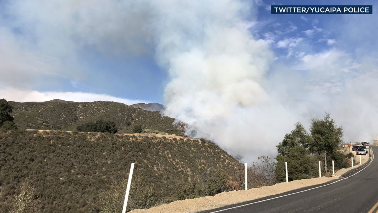 A plume of smoke billows over hillsides along Oak Glen Road in Yucaipa after a brush fire broke out in the area on Wednesday, Nov. 29, 2017.