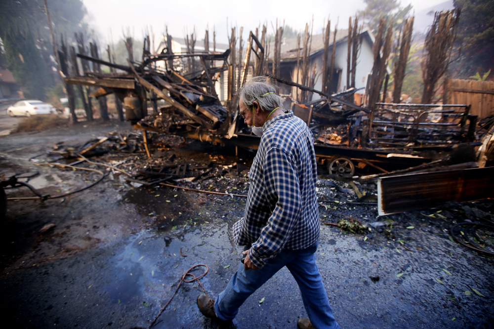 <div class='meta'><div class='origin-logo' data-origin='none'></div><span class='caption-text' data-credit='Chris Carlson/AP Photo'>Homeowner Alan Barnard walks past the remains of his RV from a wildfire in the Lake View Terrace area of Los Angeles on Tuesday, Dec. 5, 2017.</span></div>