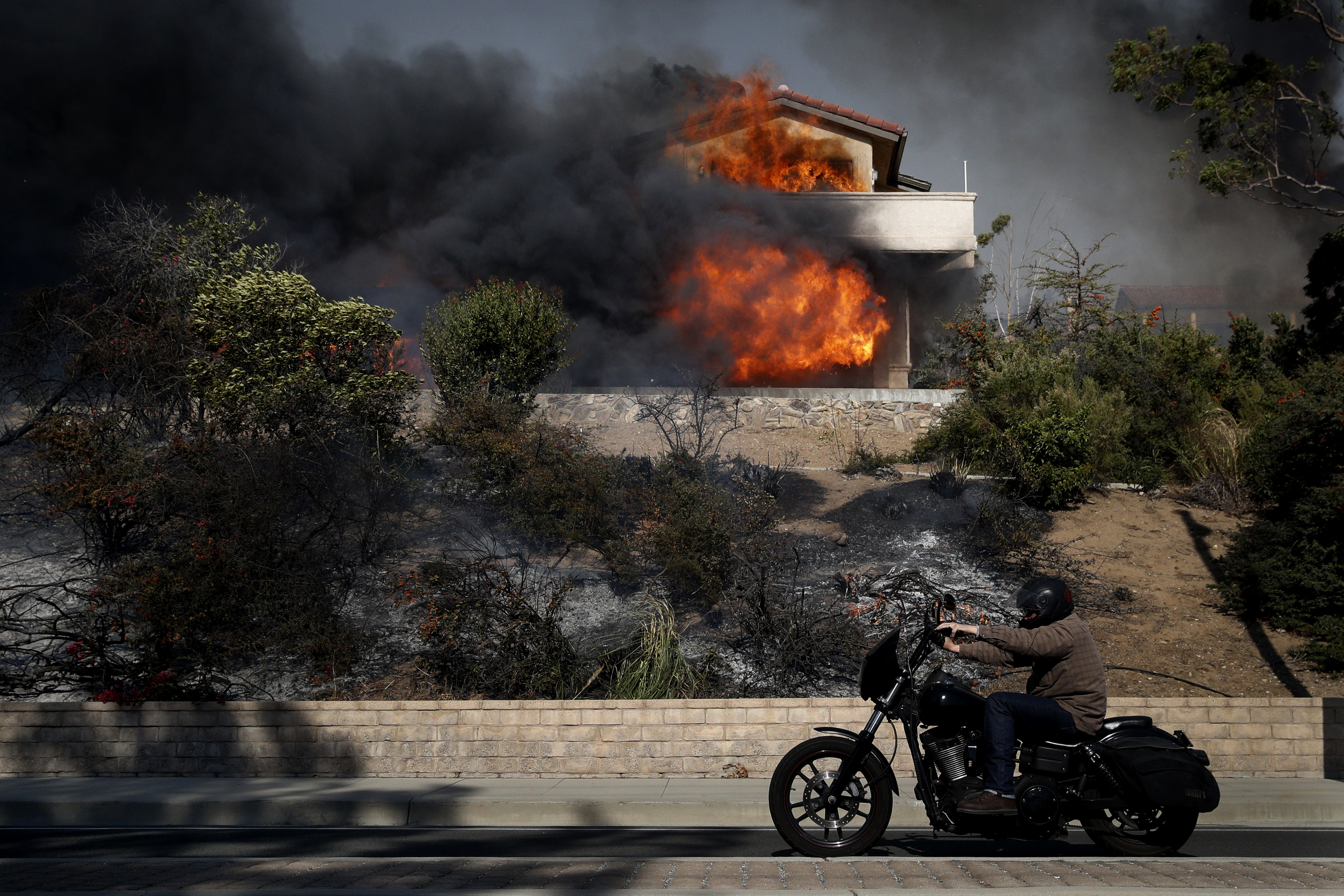 <div class='meta'><div class='origin-logo' data-origin='none'></div><span class='caption-text' data-credit='Jae C. Hong/AP Photo'>A man rides his bike past a home consumed by a wildfire Tuesday, Dec. 5, 2017, in Ventura, Calif.</span></div>