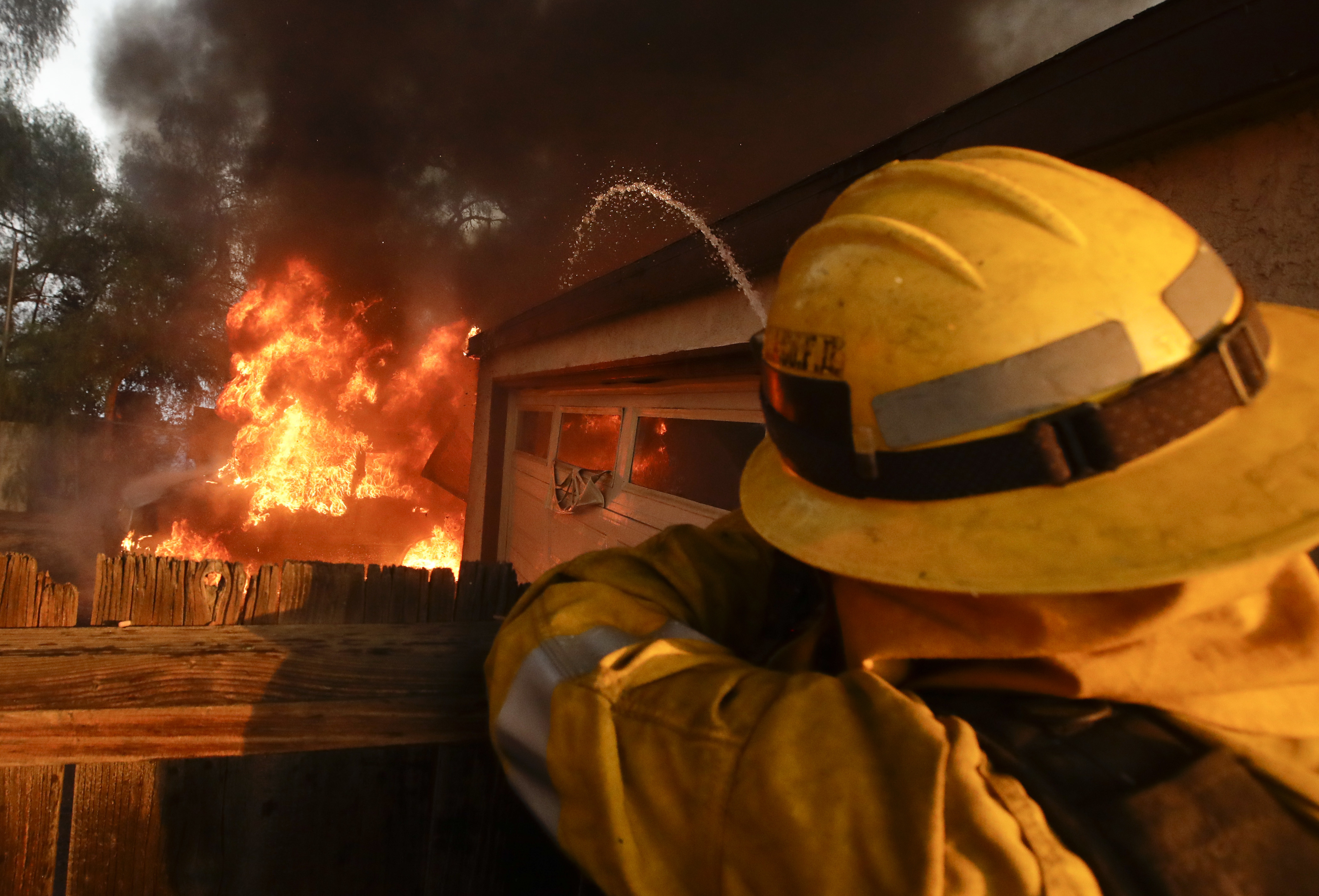 <div class='meta'><div class='origin-logo' data-origin='none'></div><span class='caption-text' data-credit='Chris Carlson/AP Photo'>A Los Angeles County firefighter puts water a burning house in a wildfire in the Lake View Terrace area of Los Angeles Tuesday, Dec. 5, 2017.</span></div>