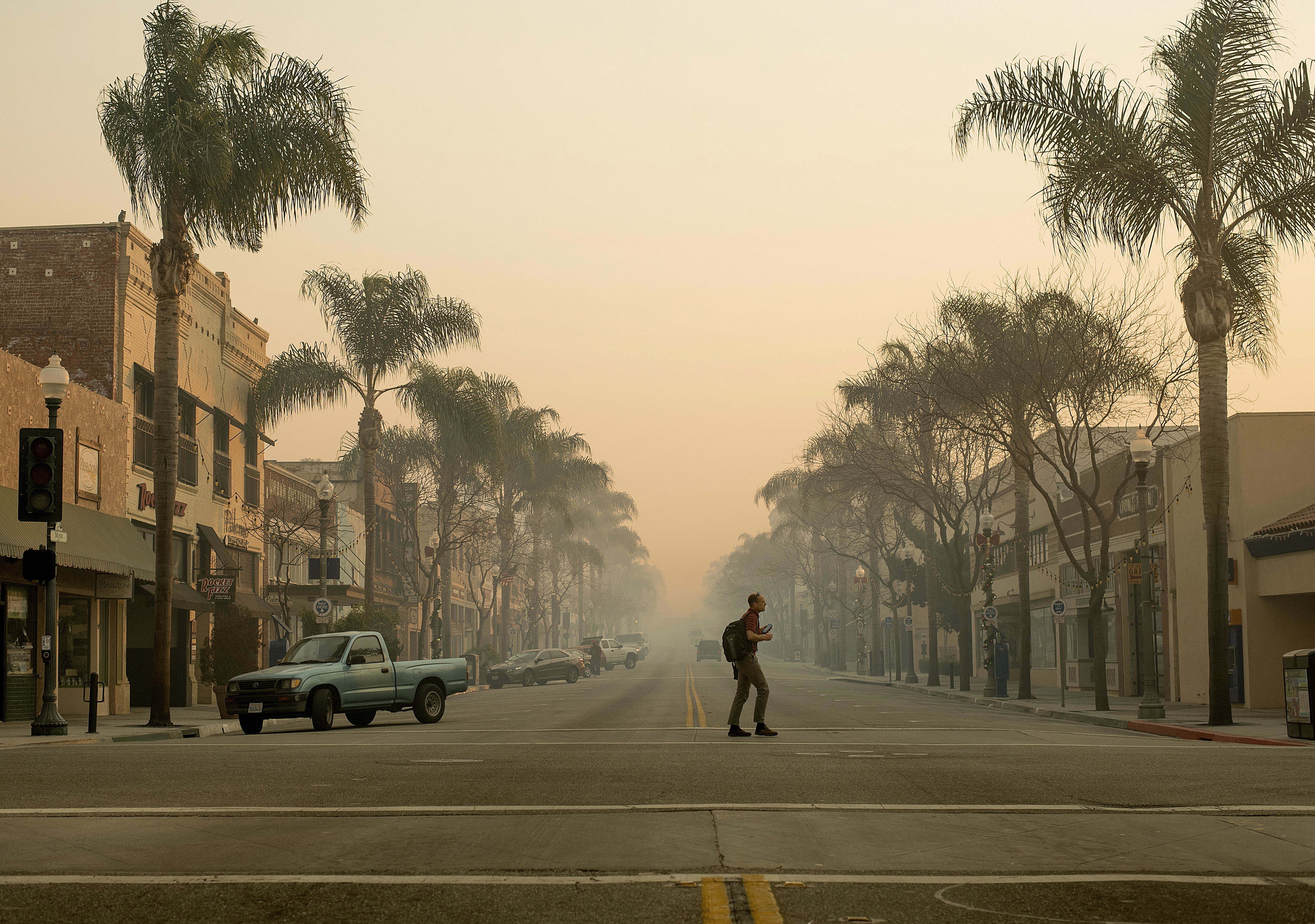 <div class='meta'><div class='origin-logo' data-origin='none'></div><span class='caption-text' data-credit='Noah Berger/AP Photo'>Smoke hangs in the air as a man crosses Main St. in Ventura, Calif., on Wednesday, Dec. 6, 2017.</span></div>