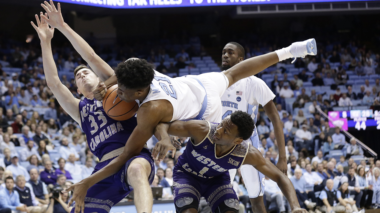 North Carolina's Sterling Manley (21) falls over Western Carolina's Onno Steger (33) and Desmond Johnson (1) during the first half in Chapel Hill on Wednesday.