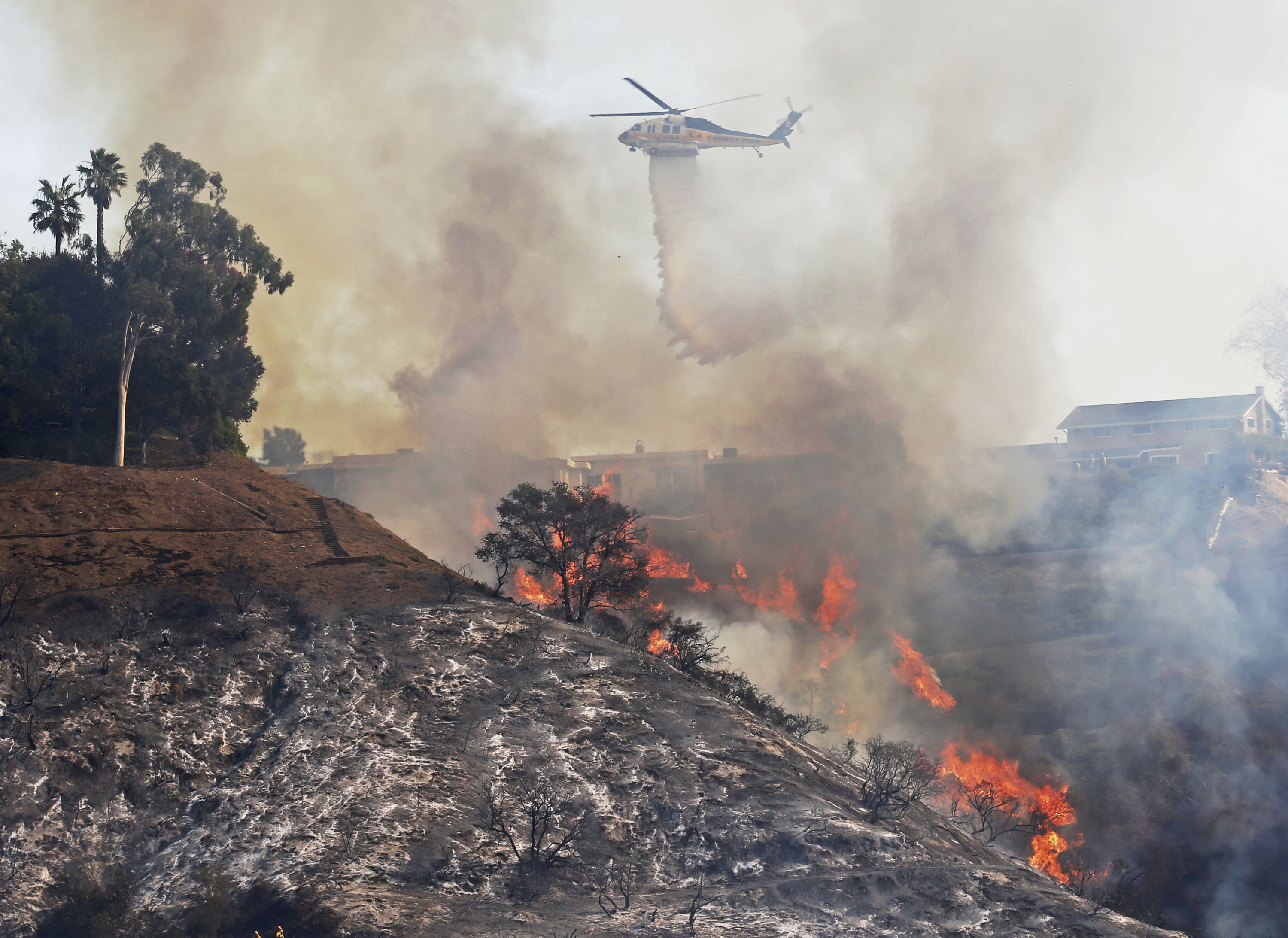 <div class='meta'><div class='origin-logo' data-origin='none'></div><span class='caption-text' data-credit='Reed Saxon/AP Photo'>A Los Angeles County Fire Dept. helicopter makes a water drop on flames sweeping up a steep canyon wall, threatening homes on a ridge line in the Bel Air district of Los Angeles.</span></div>