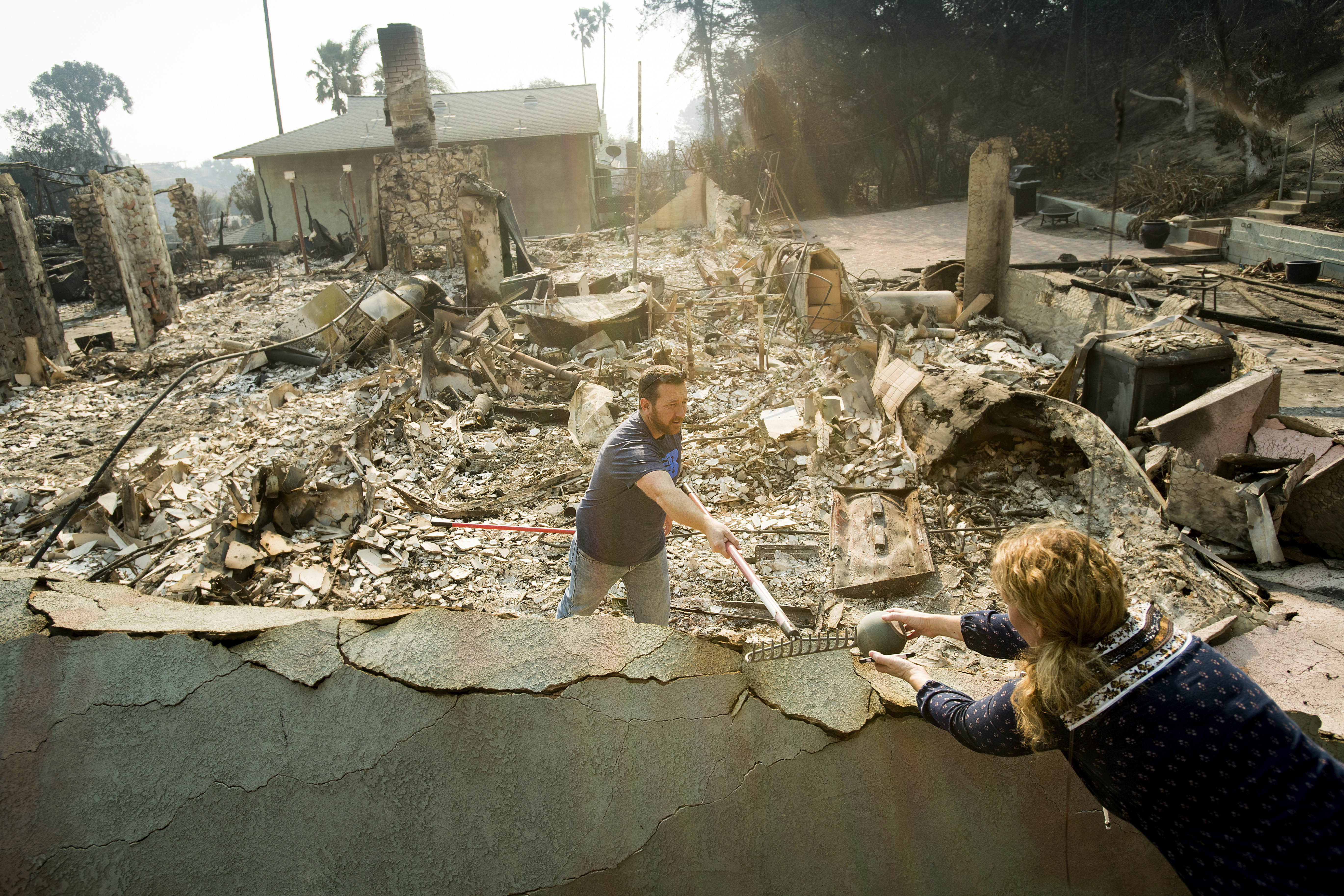 <div class='meta'><div class='origin-logo' data-origin='none'></div><span class='caption-text' data-credit='Noah Berger/AP Photo'>Paul Mattesich hands a jar to his wife Erica Mattesich while sifting through rubble at his family's Ventura, Calif., home following a  wildfire on Wednesday, Dec. 6, 2017.</span></div>