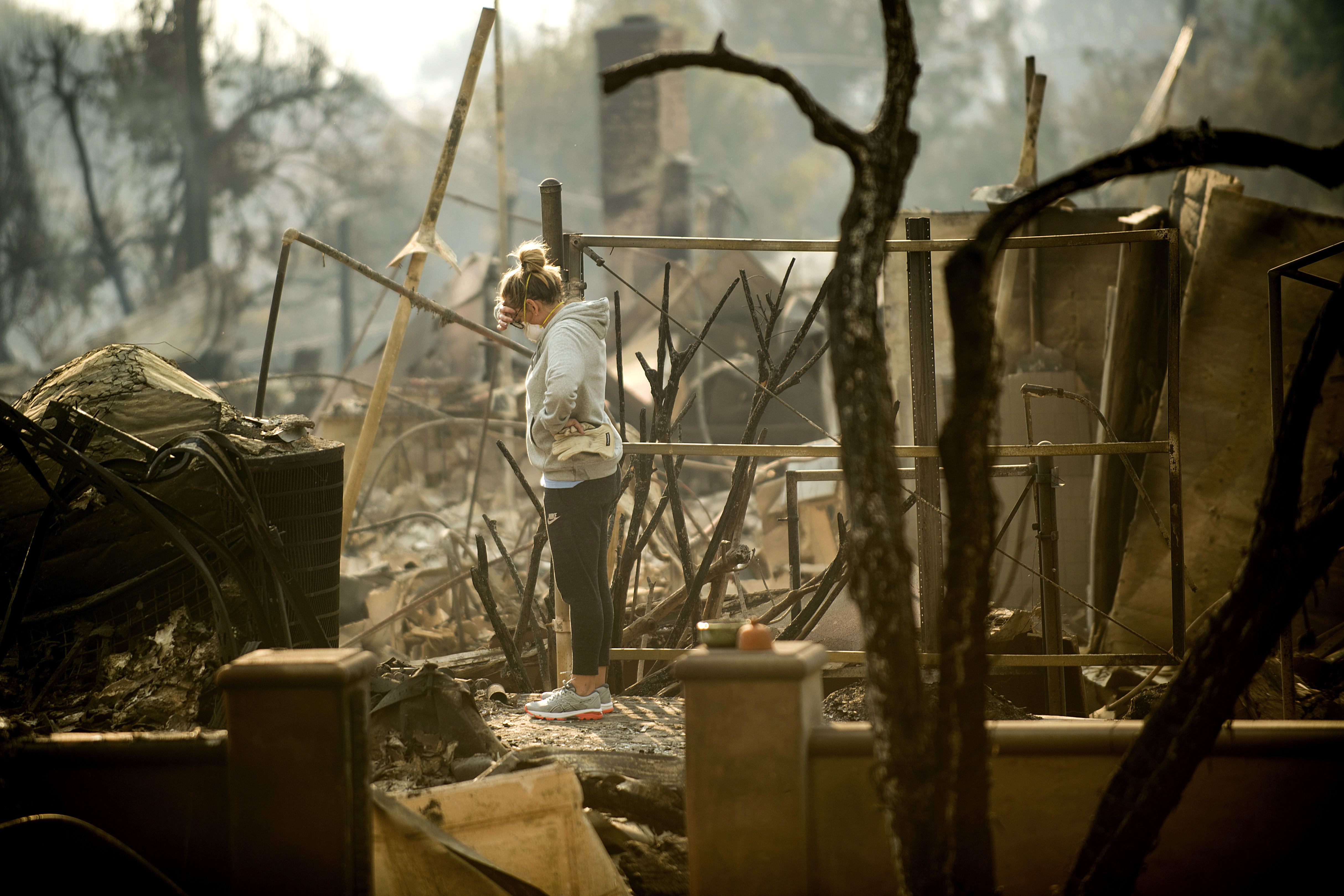 <div class='meta'><div class='origin-logo' data-origin='none'></div><span class='caption-text' data-credit='Noah Berger/AP Photo'>Bree Laubacher pauses while sifting through rubble at her Ventura, Calif., home following a wildfire on  Dec. 6. A barbecue smoker and her son's batting cage survived the blaze.</span></div>