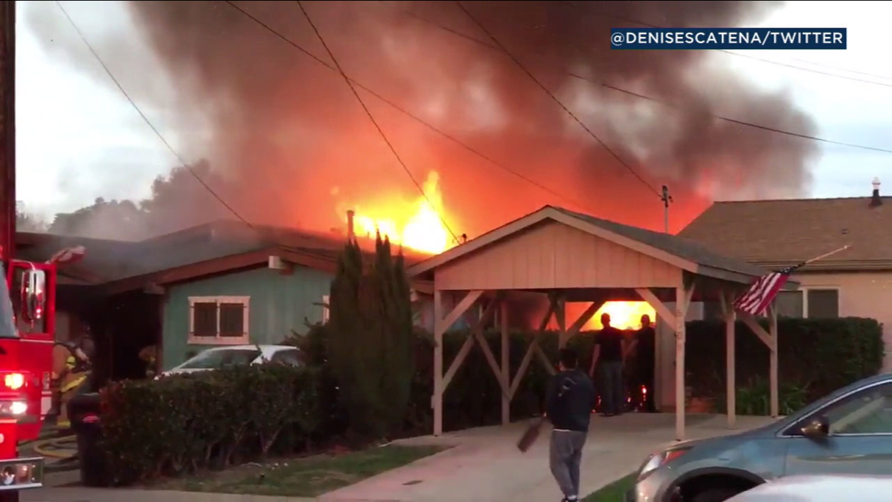The back of a home is seen engulfed in flames after a small plane crashed into it on Saturday, Dec. 9, 2017.