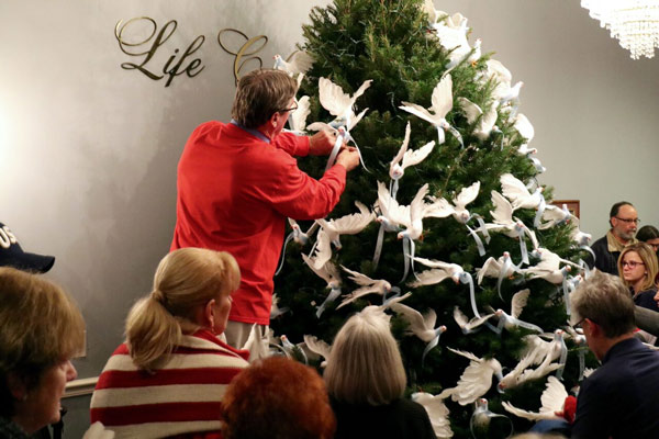 "<div class=""meta image-caption""><div class=""origin-logo origin-image none""><span>none</span></div><span class=""caption-text"">Life Celebration by Givnish staff helps Memorial Tree Service attendees place their white dove on the tree in honor of their loved ones</span></div>"