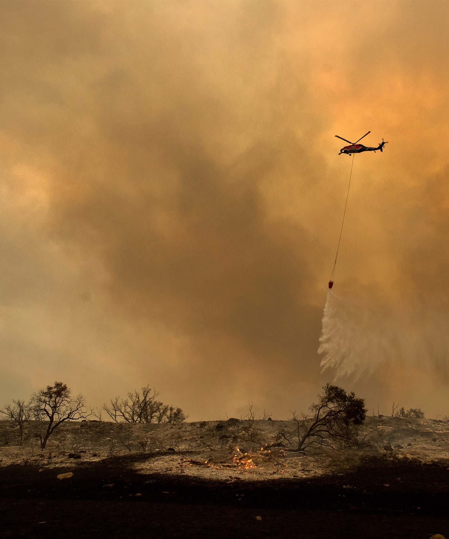 <div class='meta'><div class='origin-logo' data-origin='AP'></div><span class='caption-text' data-credit='AP Photo/Noah Berger'>A helicopter drops water while trying to keep a wildfire from jumping Santa Ana Road near Ventura, Calif., on Saturday, Dec. 9, 2017.</span></div>
