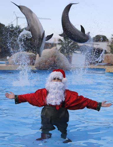 "<div class=""meta image-caption""><div class=""origin-logo origin-image none""><span>none</span></div><span class=""caption-text"">A man dressed as Santa Claus poses for photographers with two dolphins, at the Marineland animal exhibition park in Antibes, southeastern France. (AP Photo/Lionel Cironneau)</span></div>"