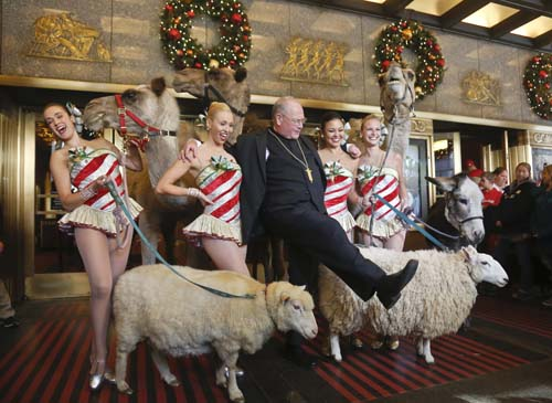 "<div class=""meta image-caption""><div class=""origin-logo origin-image none""><span>none</span></div><span class=""caption-text"">Cardinal Timothy Dolan, center, kicks his leg as he poses with members of the Radio City Rockettes, after he blessed camels, sheep and a donkey,  in New York. (AP Photo/Bebeto Matthews)</span></div>"
