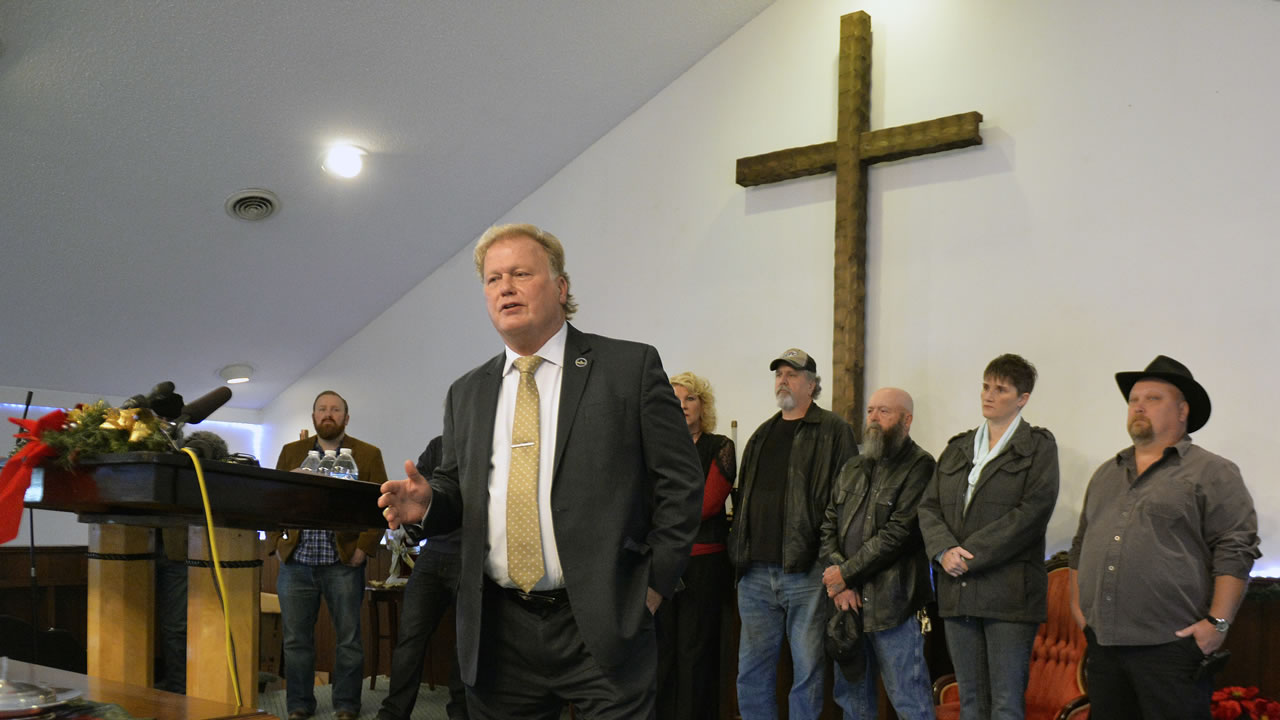 With friends and family standing behind him, Kentucky State Rep., Republican Dan Johnson addresses the public from his church on Tuesday, Dec. 12, 2017.