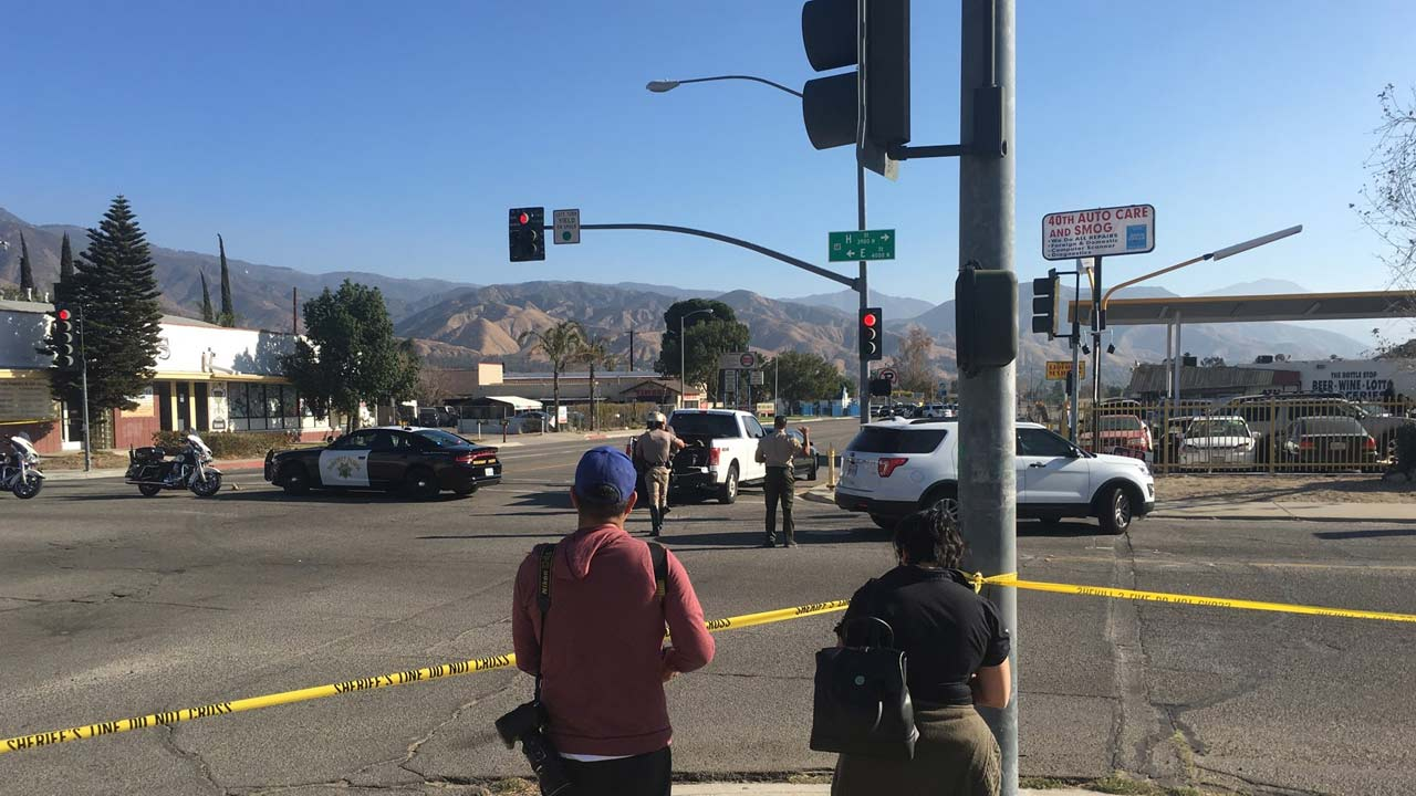 Law enforcement officials are seen in San Bernardino, where a man was reported to be holding a gun to his head on Thursday, Dec.14, 2017.
