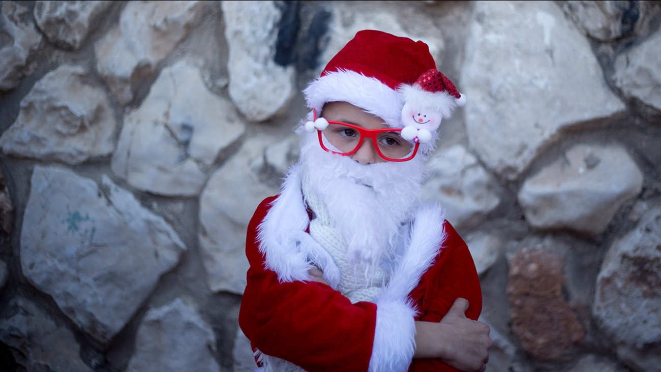 FILE - 2015 An Israeli Arab Christian boy dressed up as Santa Claus waits for the start of the annual Christmas parade in the northern Israeli city of Nazareth, Israel.