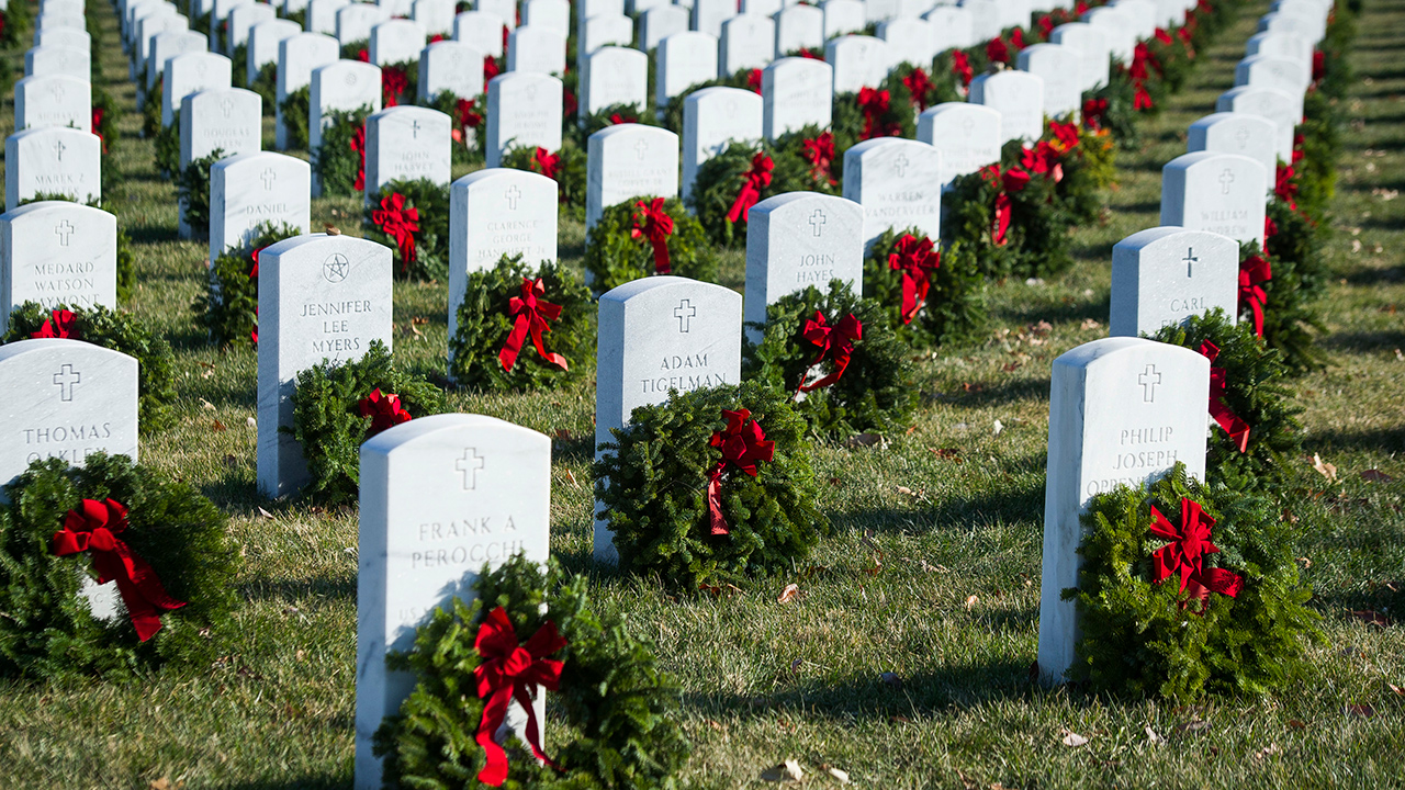 Wreaths rest against headstones at Arlington National Cemetery as Wreaths Across America places remembrance wreaths on headstones at the cemetery in Arlington, Va.
