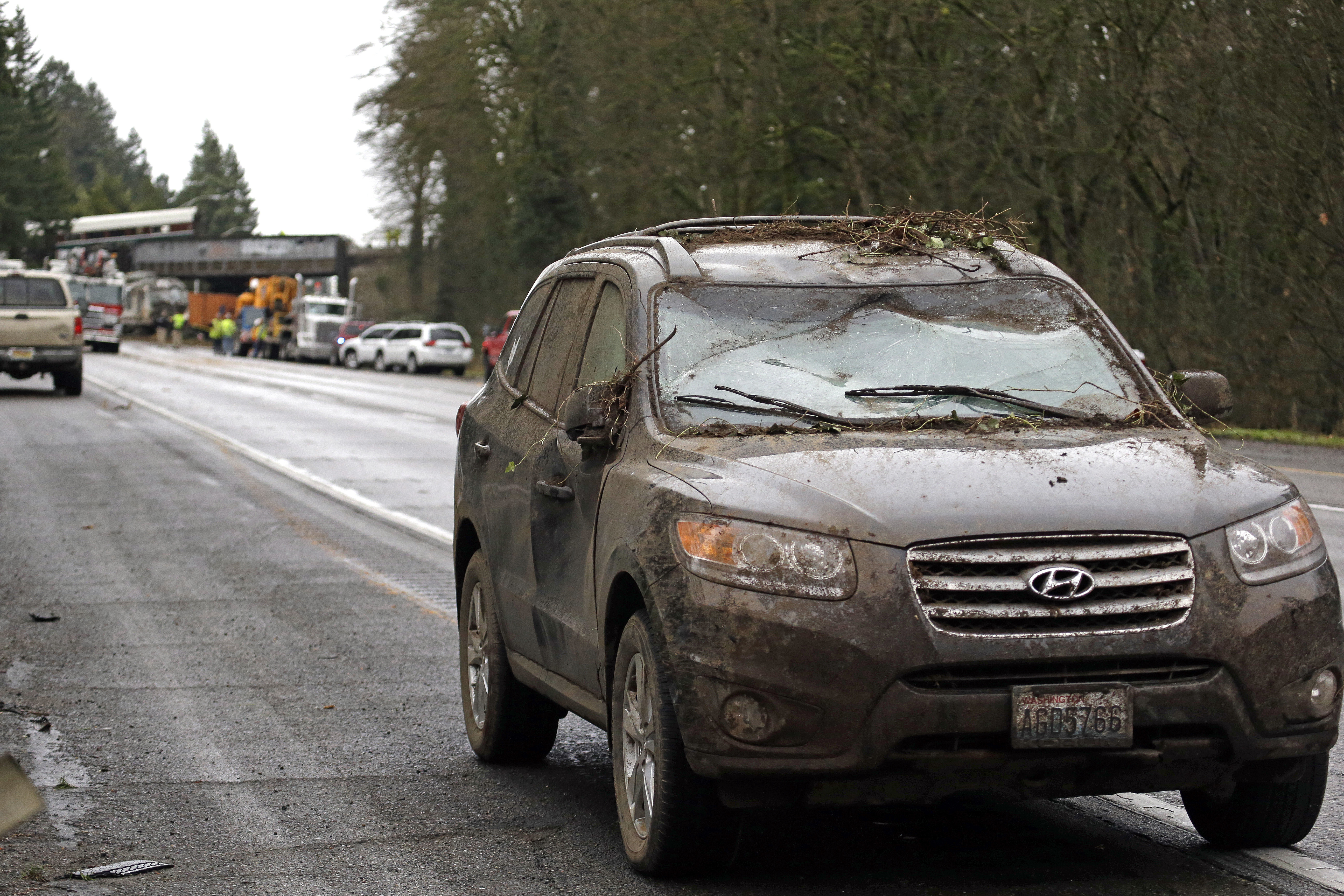 <div class='meta'><div class='origin-logo' data-origin='none'></div><span class='caption-text' data-credit='Elaine Thompson/AP Photo'>A car covered in mud and debris and with a smashed windshield and other damage sits parked on the shoulder just beyond where an Amtrak train lay spilled onto Interstate 5 below.</span></div>
