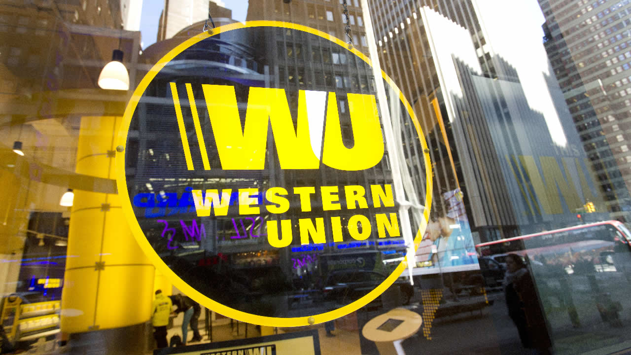 Midtown buildings are reflected in the window of a Western Union store, Wednesday, April 5, 2016 in New York. (AP Photo/Mark Lennihan)