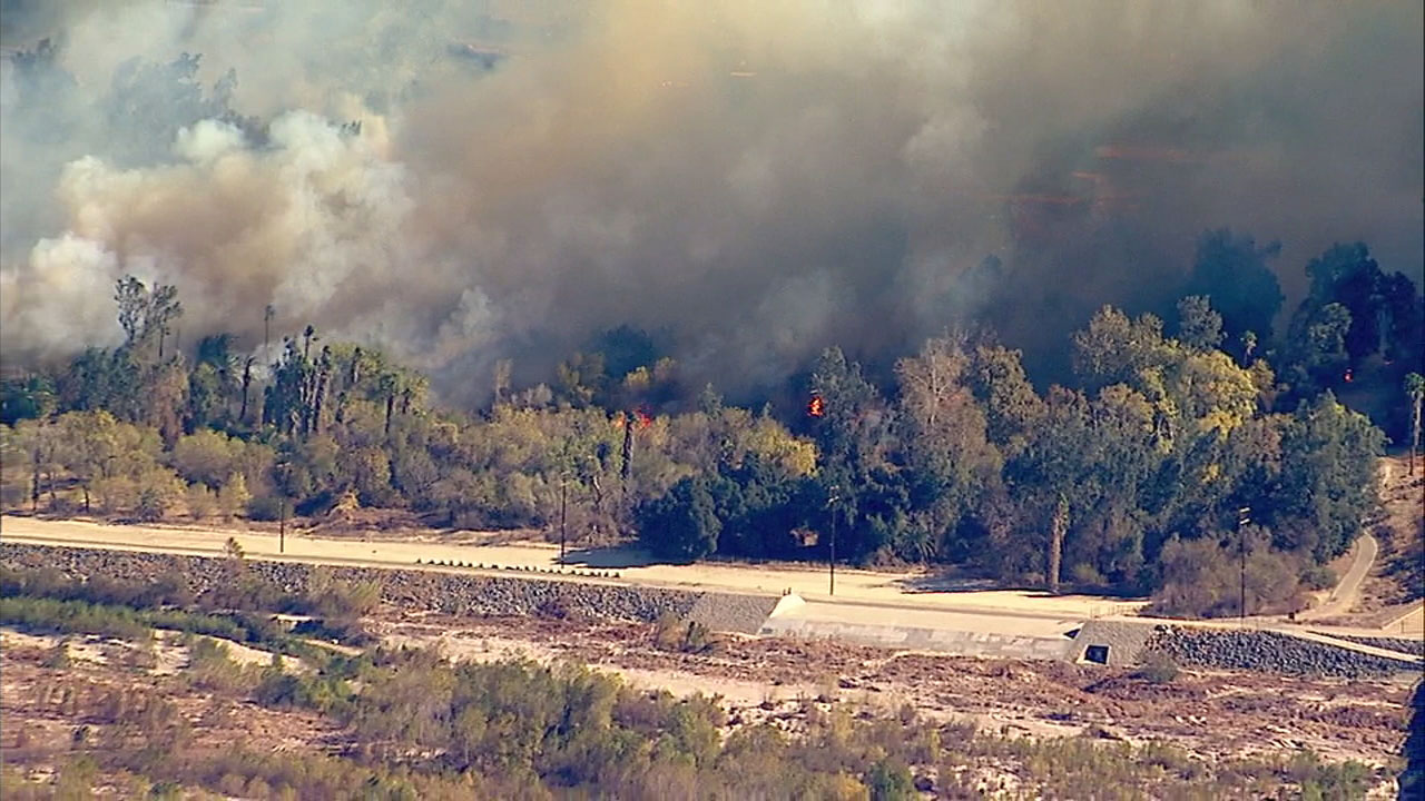 Smoke and flames cover acres of land near the Santa Ana river bottom in Riverside on Thursday, Dec. 21, 2017.
