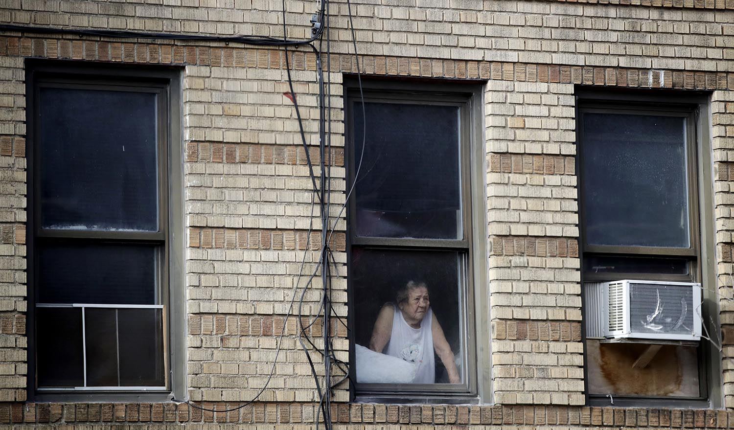 """<div class=""""meta image-caption""""><div class=""""origin-logo origin-image ap""""><span>AP</span></div><span class=""""caption-text"""">A woman looks out the window of a building adjacent to an apartment building where more than 10 people died in fire a day earlier in the Bronx. (AP Photo/Julio Cortez)</span></div>"""