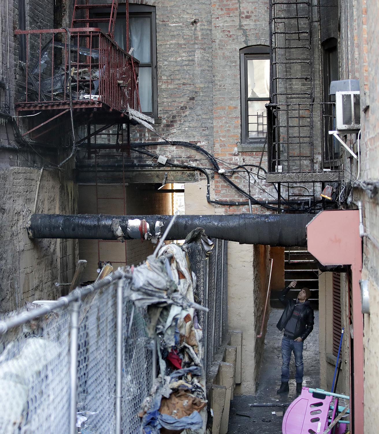 """<div class=""""meta image-caption""""><div class=""""origin-logo origin-image ap""""><span>AP</span></div><span class=""""caption-text"""">A man uses a cell phone to take images of an apartment building where more than 10 people died in fire a day earlier in the Bronx borough of New York, Friday, Dec. 29, 2017. (AP Photo/Julio Cortez)</span></div>"""