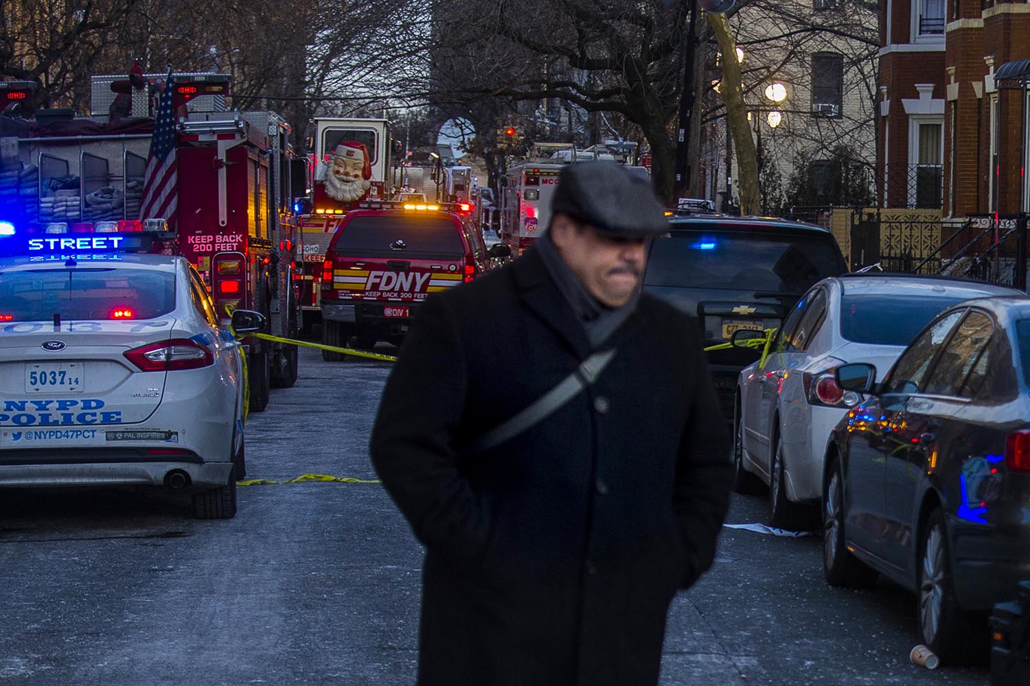 """<div class=""""meta image-caption""""><div class=""""origin-logo origin-image ap""""><span>AP</span></div><span class=""""caption-text"""">A resident leaves the scene Friday, Dec. 29, 2017, near the building where more than 10 people died in a fire on Thursday, in the Bronx borough of New York. (AP Photo/Andres Kudacki)</span></div>"""
