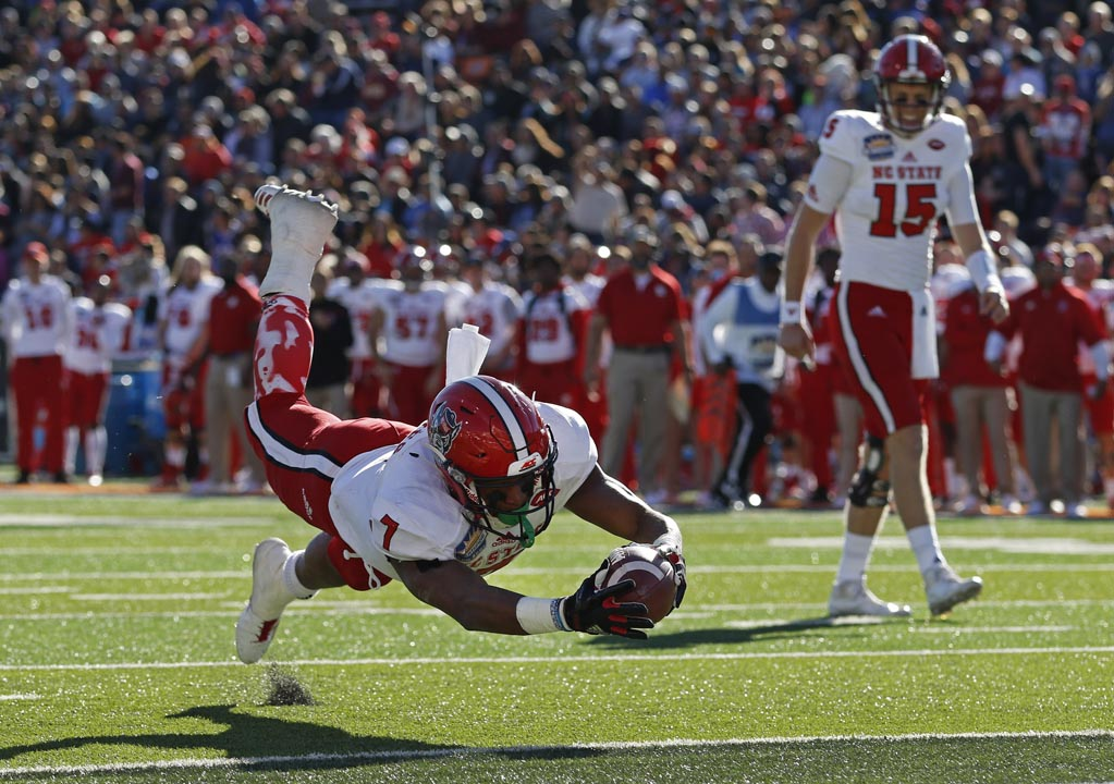 <div class='meta'><div class='origin-logo' data-origin='AP'></div><span class='caption-text' data-credit='Andres Leighton'>North Carolina State running back Nyheim Hines (7) dives into the end zone to score a touchdown against Arizona State in the Sun Bowl.</span></div>