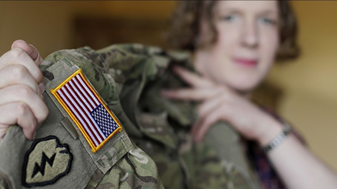 In this July 29, 2017 photo transgender U.S. army captain Jennifer Sims lifts her uniform during an interview with The Associated Press in Beratzhausen near Regensburg, Germany.