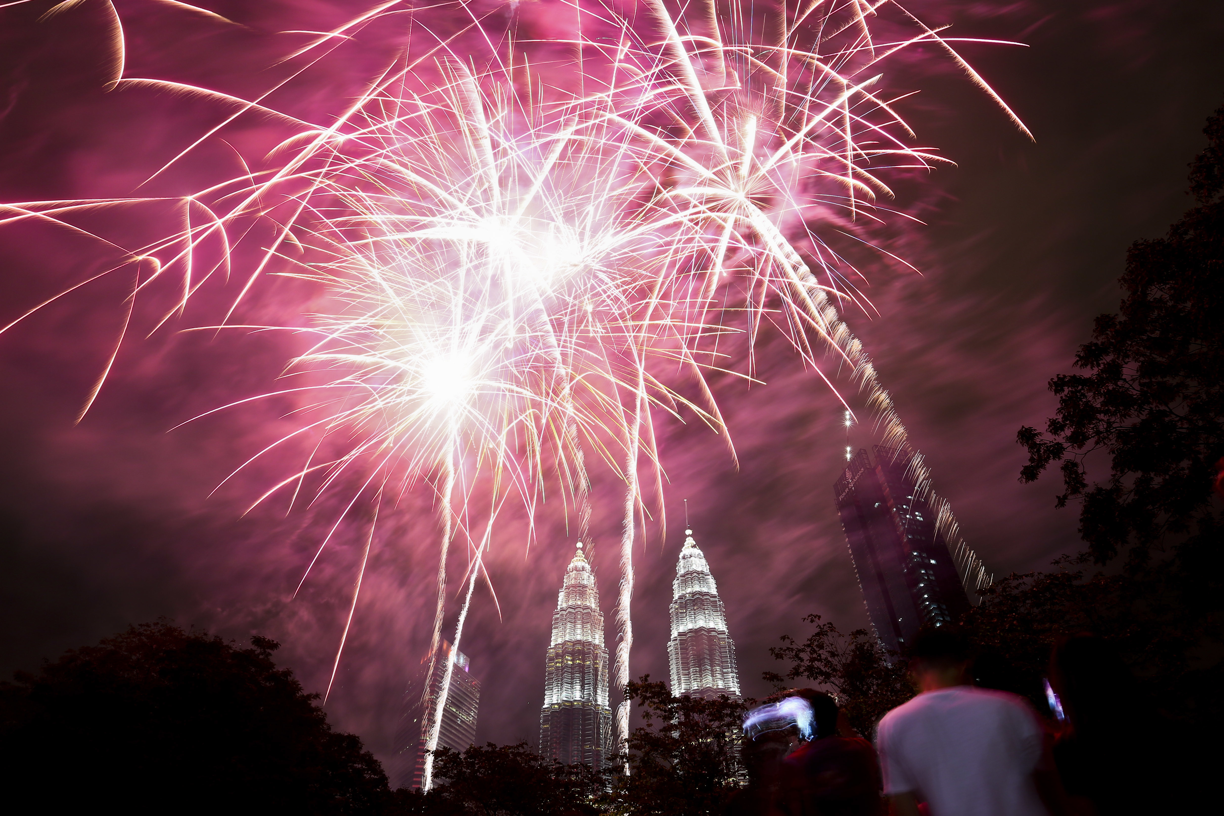 <div class='meta'><div class='origin-logo' data-origin='AP'></div><span class='caption-text' data-credit='AP Photo/Sadiq Asyraf'>People watch a fireworks display in front of Malaysia's landmark building, the Petronas Twin Towers, during the New Year's celebration in Kuala Lumpur, Malaysia.</span></div>