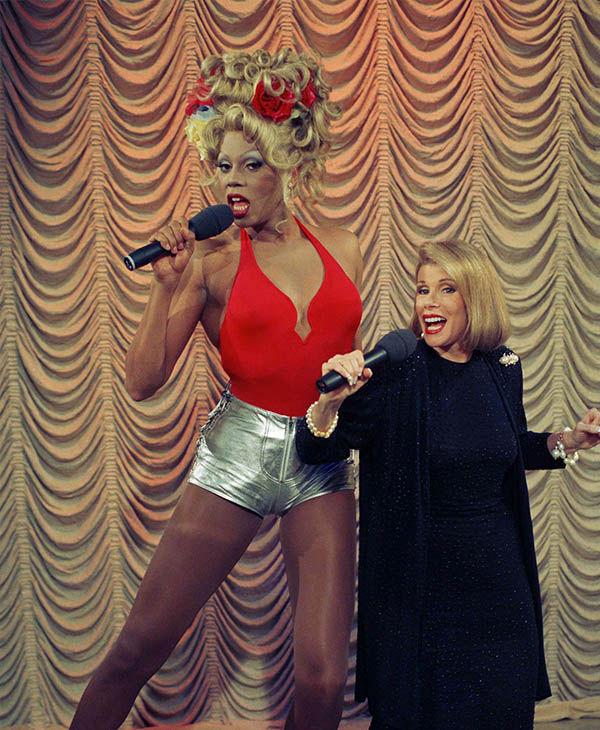 """<div class=""""meta image-caption""""><div class=""""origin-logo origin-image """"><span></span></div><span class=""""caption-text"""">Joan performing alongside drag queen RuPaul in July 1993. (Jim Cooper / AP)</span></div>"""