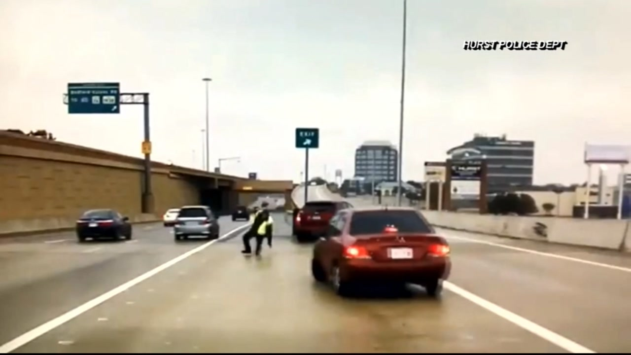 Car narrowly misses Texas officer who slips on icy road | abc13.com