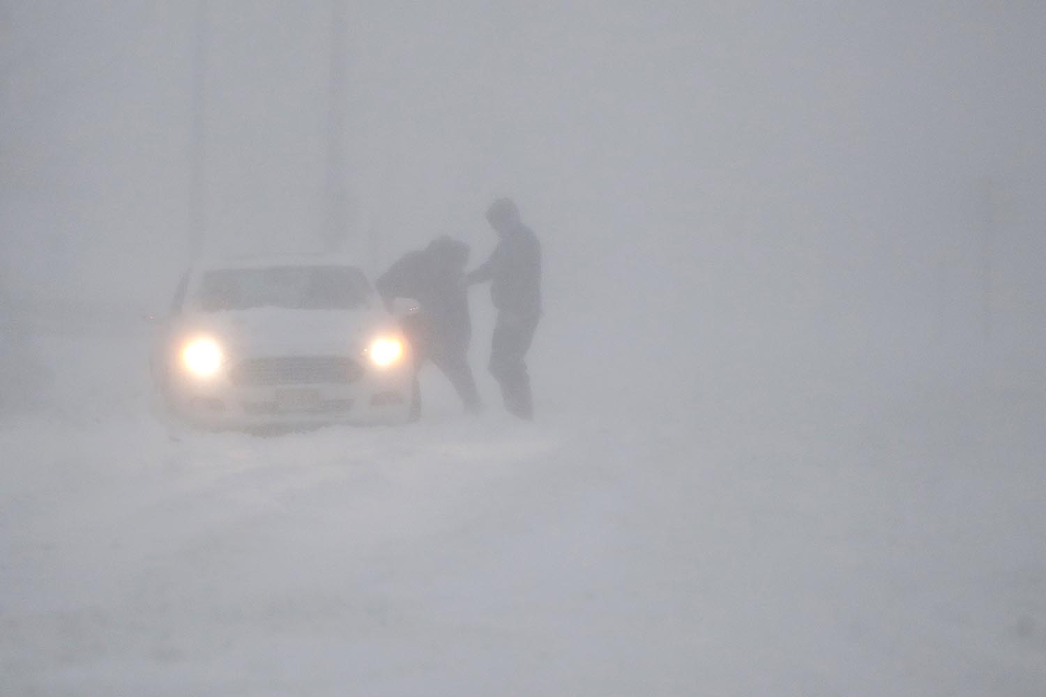 <div class='meta'><div class='origin-logo' data-origin='AP'></div><span class='caption-text' data-credit='AP Photo/Julio Cortez'>People try to clear snow off after being stuck on a snowbank on the Garden State Parkway in whiteout conditions during a snowstorm, Thursday, Jan. 4, 2018, in Tinton Falls, N.J.</span></div>